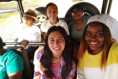 Five young women sit in the back two seats of a large, windowless vehicle