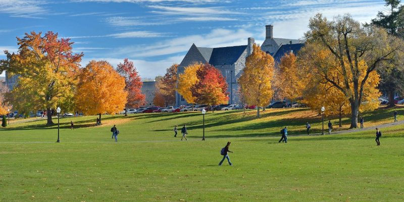 Several people walking across the Virginia Tech Drillfield with trees in fall color and campus buildings in the background.