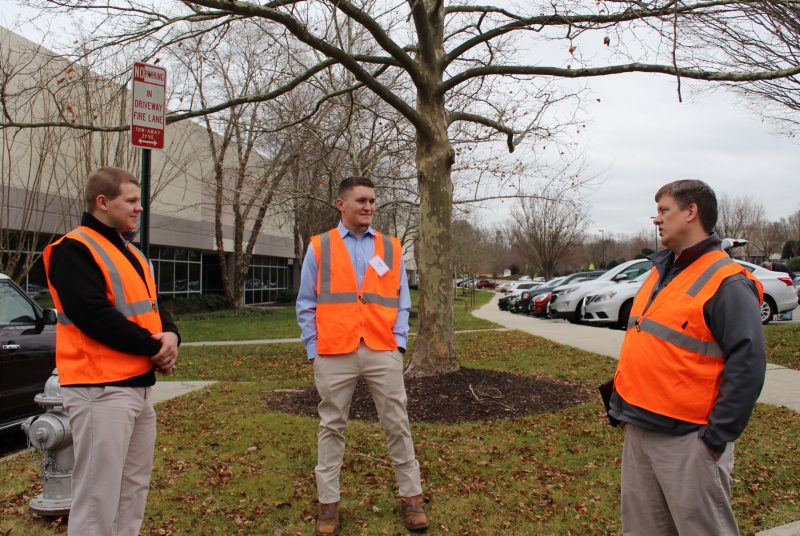 Three men stand outside an office building wearing orange reflective vests.