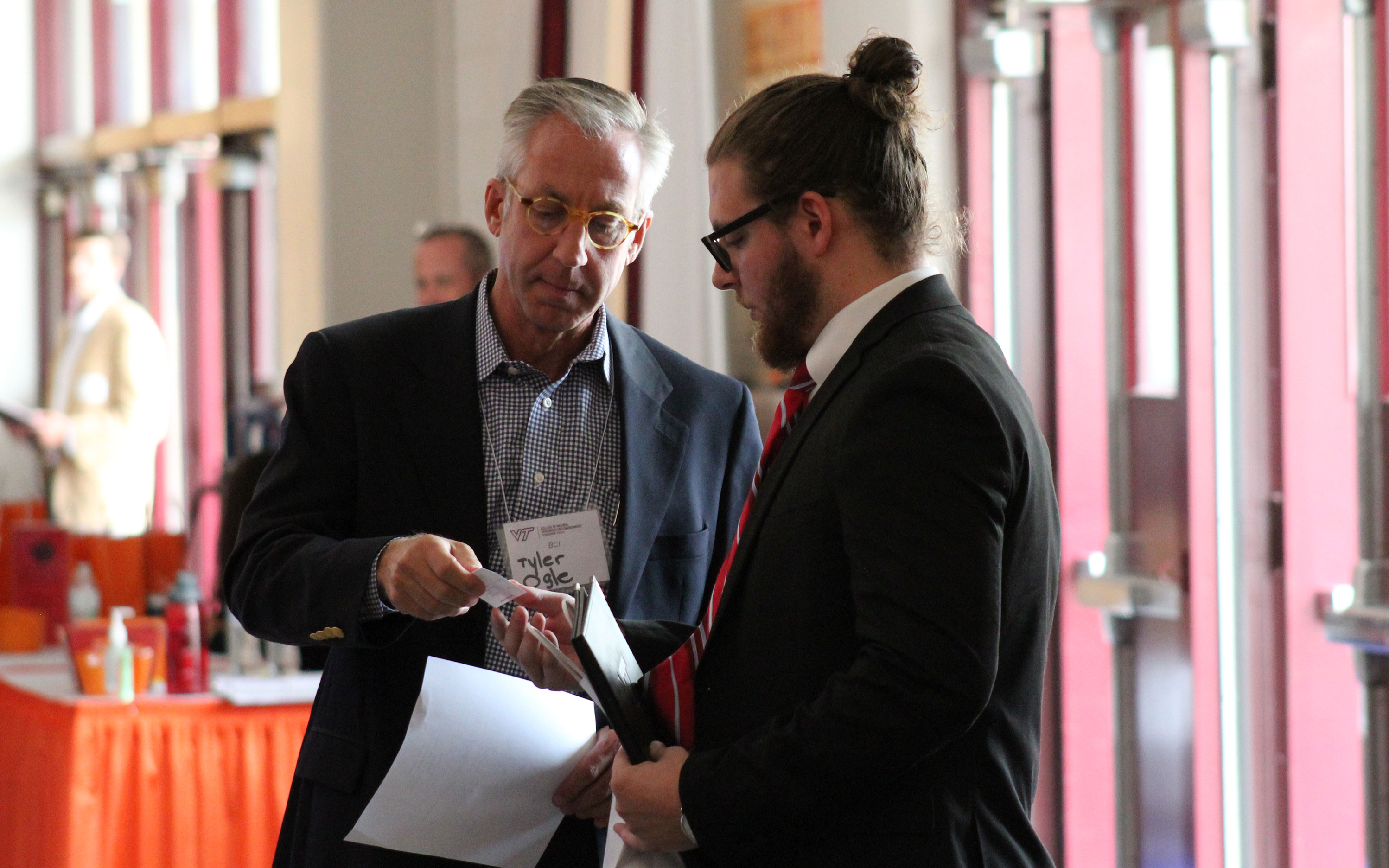 An employer handing a business card to a student at a career fair.