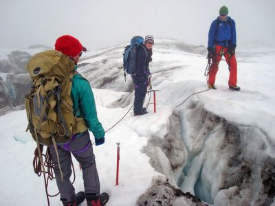 Students Sidney Burleson (left) and Bonnie Long (center), and Nate Furman of the American Alpine Institute negotiate a crevasse on the Coleman Glacier.