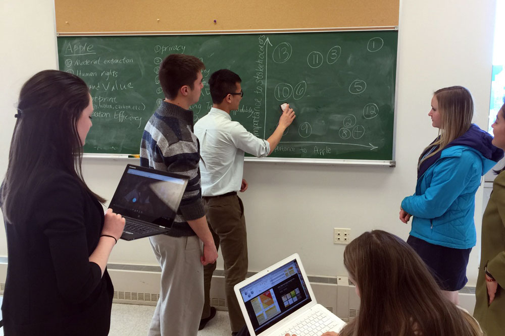 A student writes on the chalkboard while other students participate.