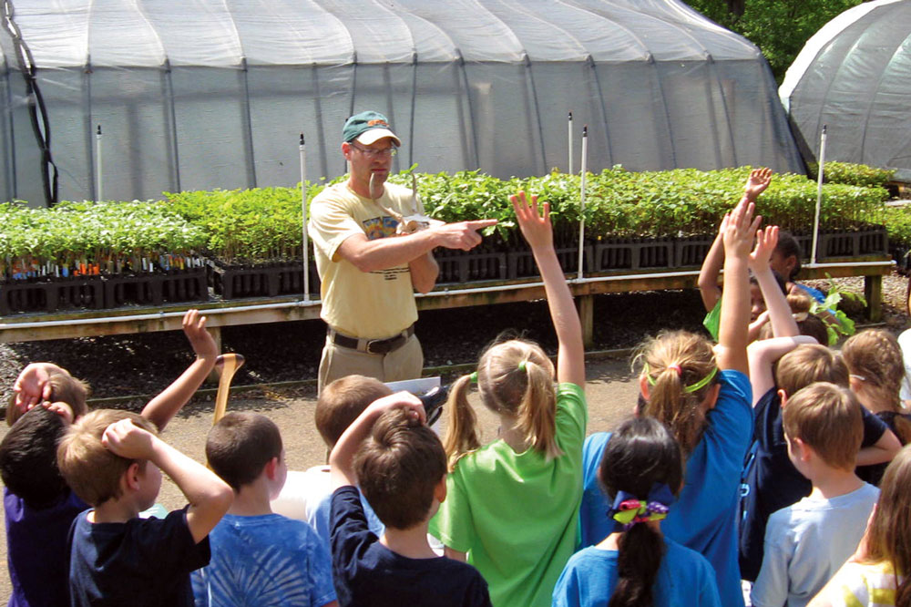 Kyle Peer talking to a group of primary school students in front of a greenhouse