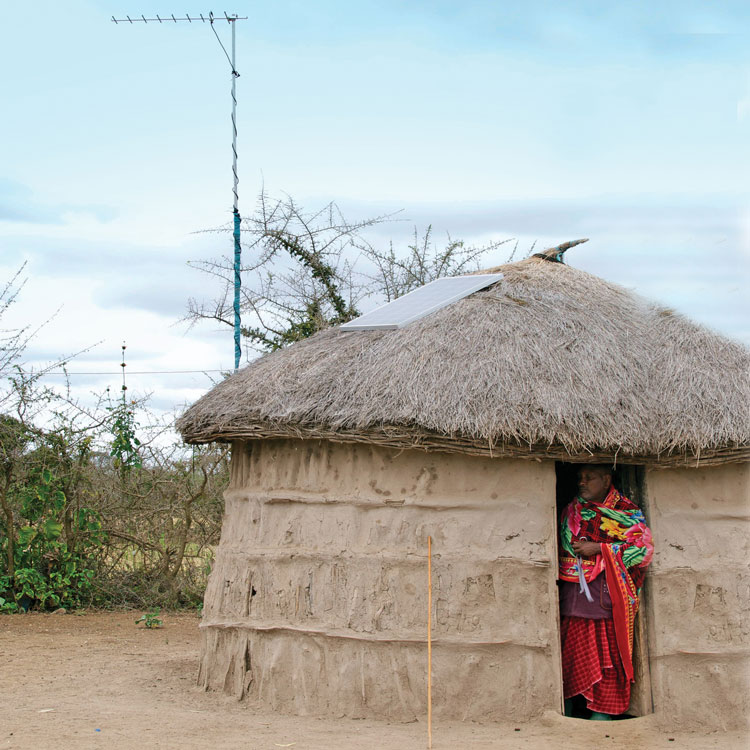 Maasai man stands in doorway of hut with solar panel and antenna on roof