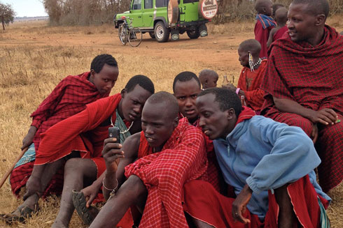 A group of young Maasai crowd around a cellphone to look at photos