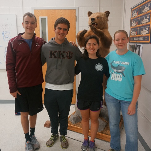 Four students standing in front of a stuffed standing bear in a classroom.