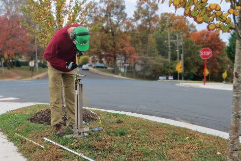 A man between a street and a sidewalk uses a specialized probe to extract a column of soil.