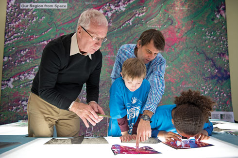 Two professors pointing out features on a photography to children.