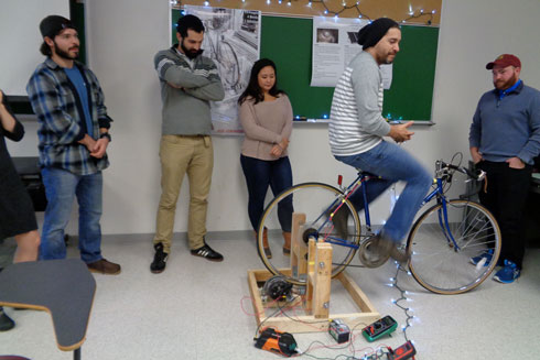 Student pedaling a bicycle generating power.