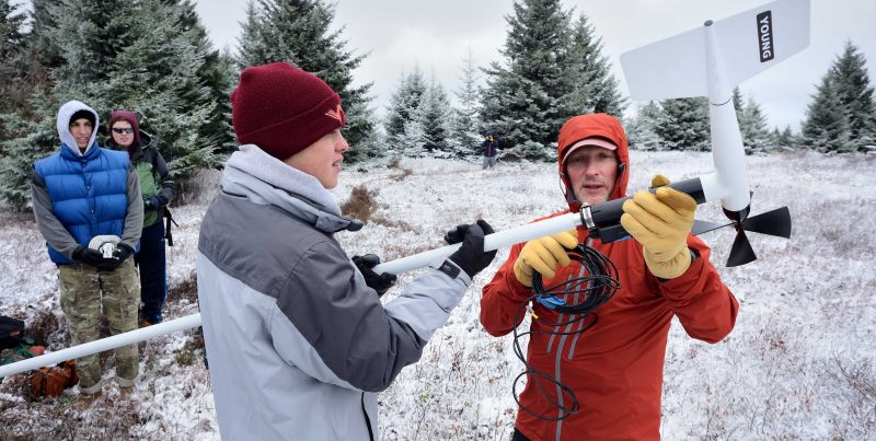 Two people in winter clothing hold a long piece of equipment. Two other people stand in the background watching them.