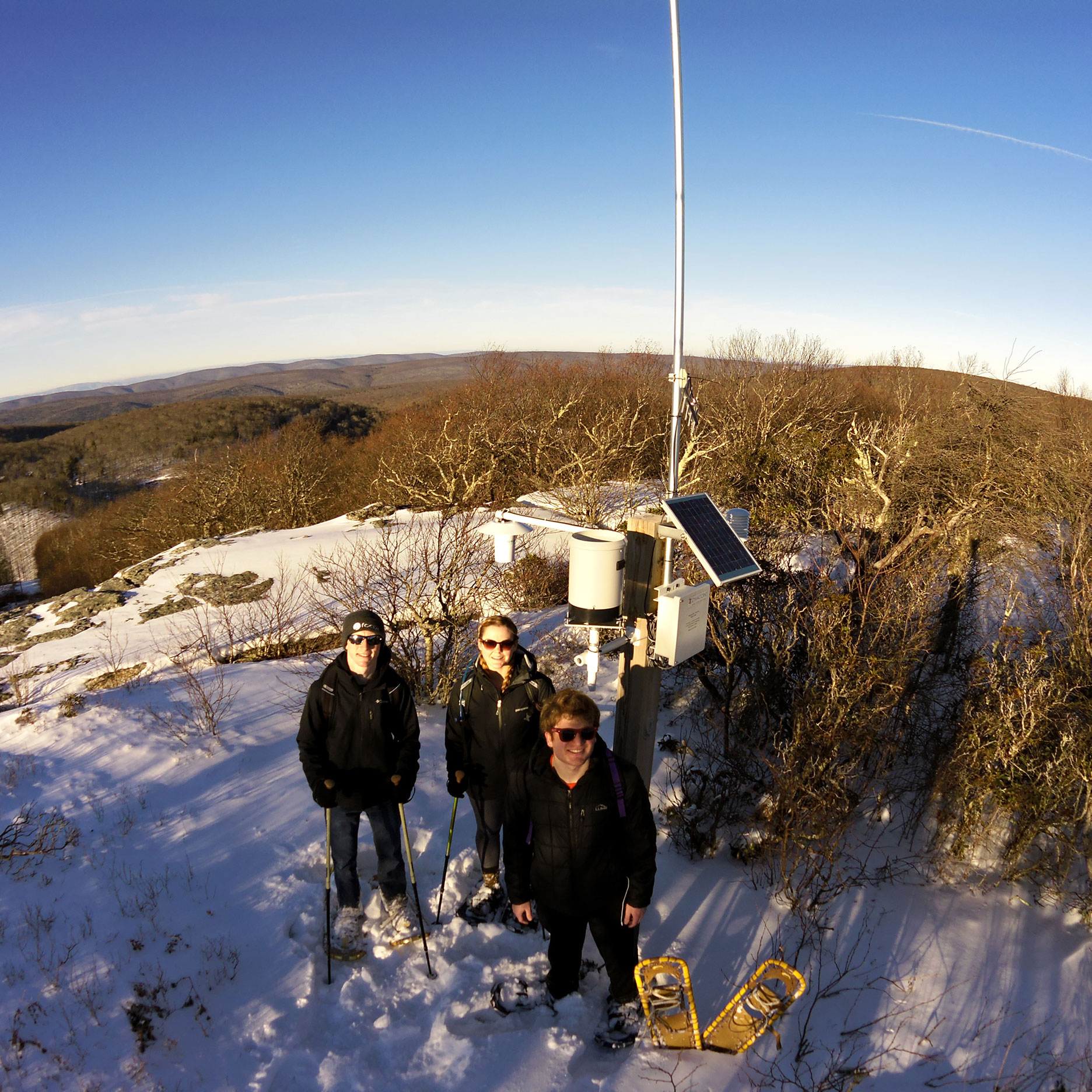 Three people stand in front of a weather station on a mountaintop, with snow on the ground.