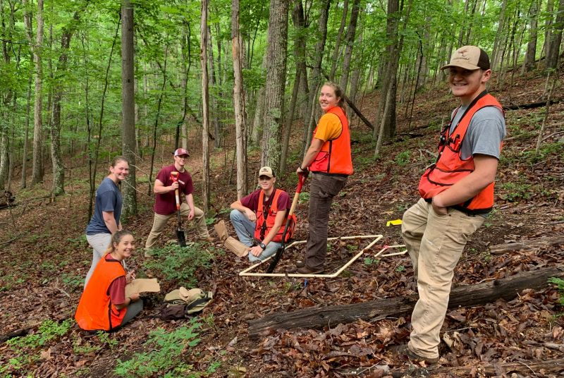 Six students (three female, three male) stand in a forested area. Several hold shovels.